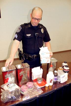 ANDREW LEIBENGUTH/TIMES NEWS Rush Township Police Sgt. Duane Frederick looks over a portion of items found in a Barnesville home. The ingredients included small batteries, aluminum foil, dye, rock salt and numerous over-the-counter items.