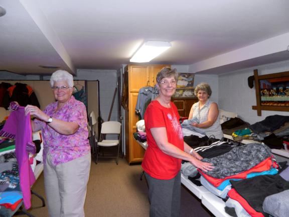 JUDY DOLGOS-KRAMER/SPECIAL TO THE TIMES NEWS Gail Malarky and Carol Lee O'Brien of Albrightsville and Shirley Leinthall of Summit Hill sort and fold some of the items donated to the fourth annual clothing Drive at St. Paul's Lutheran Church in…
