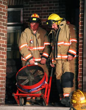 ANDREW LEIBENGUTH/TIMES NEWS Lansford firefighters Zach Gilbert, left, and Jim Kindt negotiate a large exhaust fan at the front porch to the home.