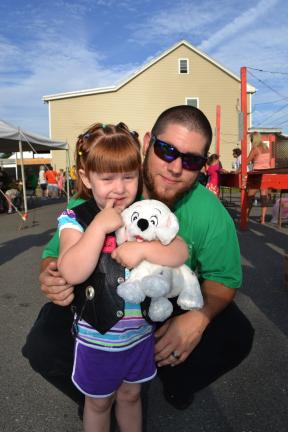 SHERI RYAN/SPECIAL TO THE TIMES NEWS @Caption Stand Alone:Wins puppy at Summit Hill festival Emily Evans, 3, of Summit Hill, displays the puppy she won at the St. Joseph's Festival in Summit Hill. Emily is pictured with her father, Edward.
