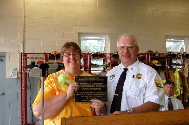 Gail Maholick/TIMES NEWS Franklin Township Fire Chief Bruce Wolfe presents a plaque to Brenda Eckley, president of the Franklin Township Fire Co. Auxiliary. The plaque will be attached to Tanker 431.