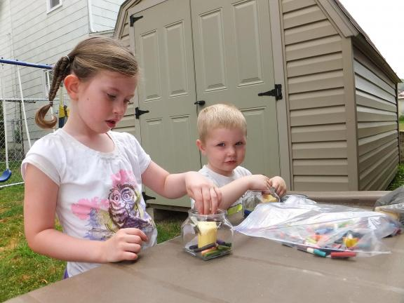 STACEY SOLT/TIMES NEWS Zoe Rodgers, 4, and Andrew Rodgers, 3, make crayon candles on a hot summer day. The craft was part of a lesson on the sun as the sun heated the crayons, they melted to create a colorful candle.