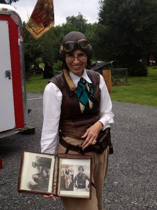 Christine Lurk holding photographs of Amelia Earhart is dressed like the aviatrix wearing jodhpurs pants and a leather helmet with Gosport communication ports, during 1940s event at the Eckley Miners Village. These ports fit over the ears of cadet…