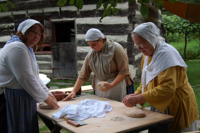 "LINDA KOEHLER/TIMES NEWS Carole Geary, Molly Maroney and Suzanne Brezina are kneading honey wheat bread dough, which will be baked in the farm's outdoor bake oven. Volunteers dress in period costume as ""family members"" of the original owners, the…"