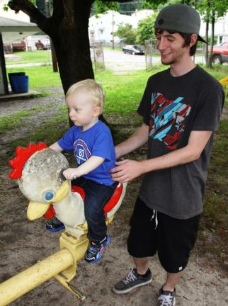 ANDREW LEIBENGUTH/TIMES NEWS Shawn Flaim of McAdoo plays with his son Sylis, 2, at Tamaqua's North and Middle Ward Park. The future of the park is uncertain due to lack of community support and funding.
