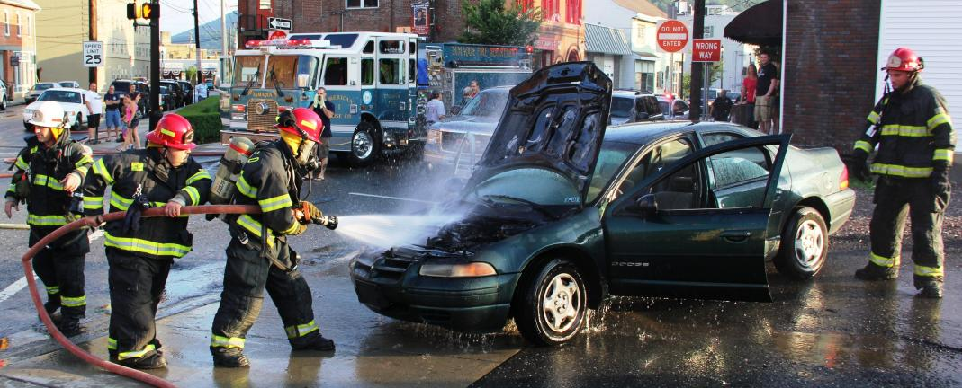 ANDREW LEIBENGUTH/TIMES NEWS Tamaqua firefighters extinguish a car fire at the intersection of Route 309 and Mauch Chunk Street at about 7 p.m. yesterday.