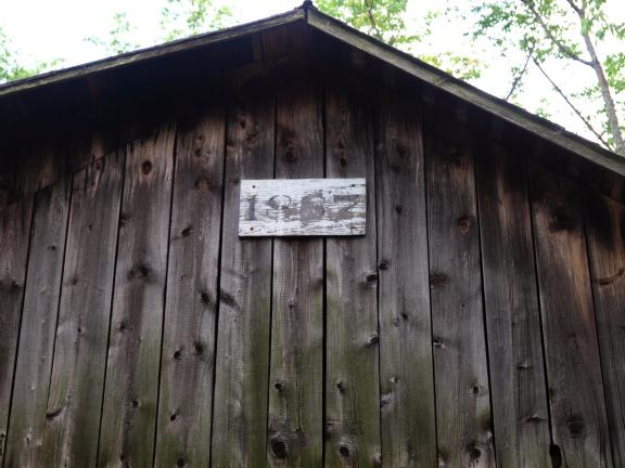 Sign on the Gehring Farm barn reads 1887. The barn once housed cows and horses, now it serves as a warehouse for old farm equipment. Note where the roof was raised on the upper left side of the barn.
