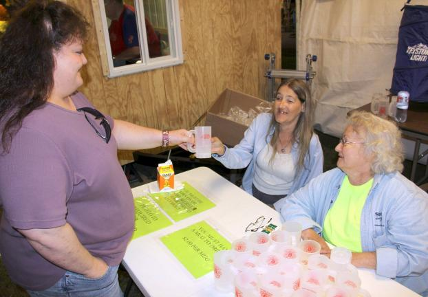 ANDREW LEIBENGUTH/TIMES NEWS During the community bazaar, Michelle Keating, of Delano, on left, receives a beer mug from Bob's daughter Christine Harris, of Quakake, and Dolly Shirey.