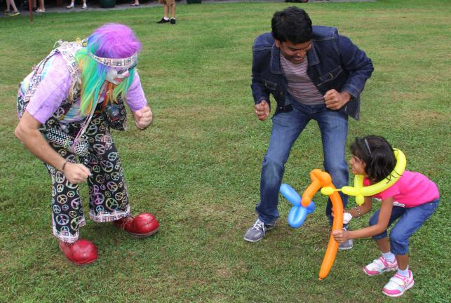 @Caption Stand Alone:Fun at miners picnic Dancing with Buster the Clown during the No. 9 Mine and Museum Picnic are Sravan Robbi and daughter Vandana, 6, of India.