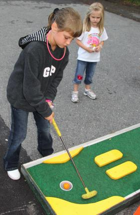 ANDREW LEIBENGUTH/TIMES NEWS Payton Selby, 4, watches as Emily Lang, 7, plays miniature golf during Rush Township's Community Day.