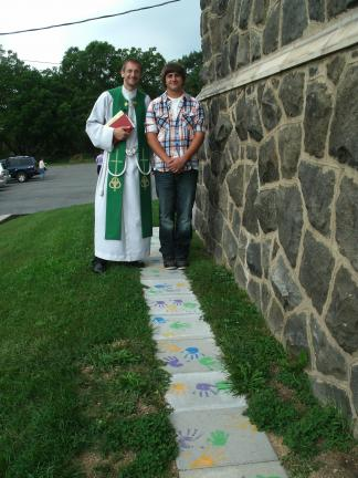 SPECIAL TO THE TIMES NEWS Corey German, right, a member of Boy Scout of Troop 145, Lehighton, and the Rev. Anthony Pagotto, stand by the pavers which were installed at Dinkey Memorial Church, Ashfield, as part of German's Eagle Scout project.
