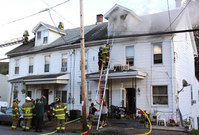 ANDREW LEIBENGUTH/TIMES NEWS Smoke billows from row homes on Valley Street in Brockton just before 6 p.m., Monday. Tuscarora Fire Chief Thomas Slane Jr. said the cause of the fire has not been determined.
