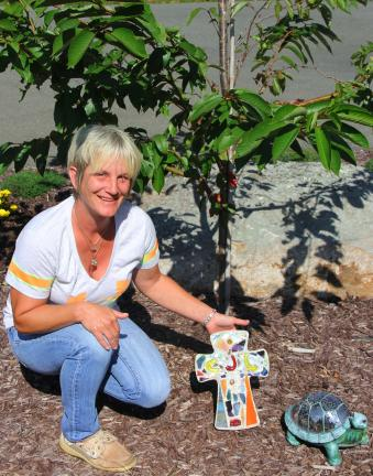 ANDREW LEIBENGUTH/TIMES NEWS Cheryl Leone kneels down next to a tree planted in the front yard of her home in honor of her daughter. Family members and friends have contributed items to the planted memorial.
