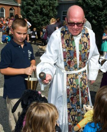 BOB FORD/TIMES NEWS @Caption Stand Alone:Blessing pets in Lehighton Fourth grader Jack Lorenz holds the holy water while the Rev. Michael Ahrensfield blesses pet, both living and stuffed during the annual pet blessing at Ss. Peter and Paul school in…