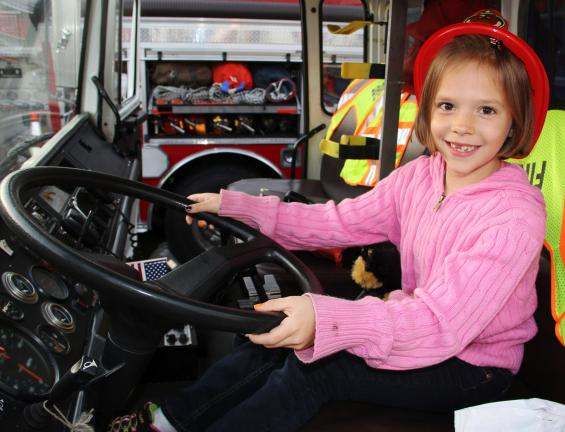 ANDREW LEIBENGUTH/TIMES NEWS @Caption Stand Alone:How it feels to be a firefighter Amber Dreher, 8, of Middleport, rides in the driver's seat of Middleport's fire truck during the Middleport Fire Company's annual fire prevention and safety fair held…
