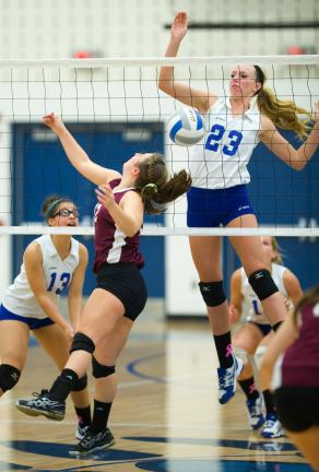 bob ford/times news Pleasant Valley's Courtney Miller (23) follows through after spiking the ball. Taylor Yurasits is the Indian player at the net.