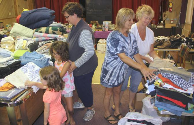 ANDREW LEIBENGUTH/TIMES NEWS Helping sort many piles of clothing and hundreds of other items during a recent donation collection are, from left, Alivia and Kailce with their mother Amanda Woodring, Ann Hadesty and Dona Hollywood.