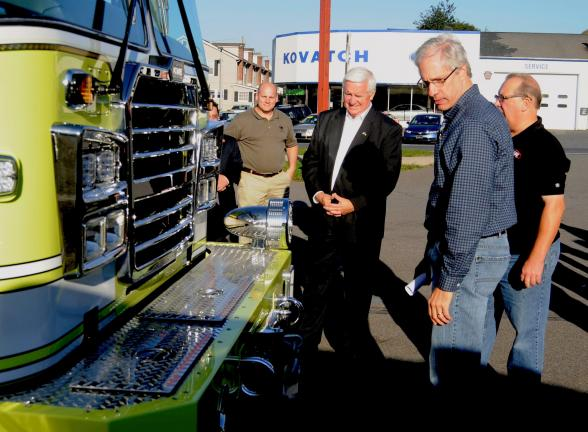 RON GOWER/TIMES NEWS Gov. Tom Corbett, second from left, looks over a finished fire truck bound for Copiague, Long Island, N.Y., during a tour of the KME Plant in Nesquehoning, Sunday. Looking on are, from left, state Rep. Doyle Heffley; attorney…
