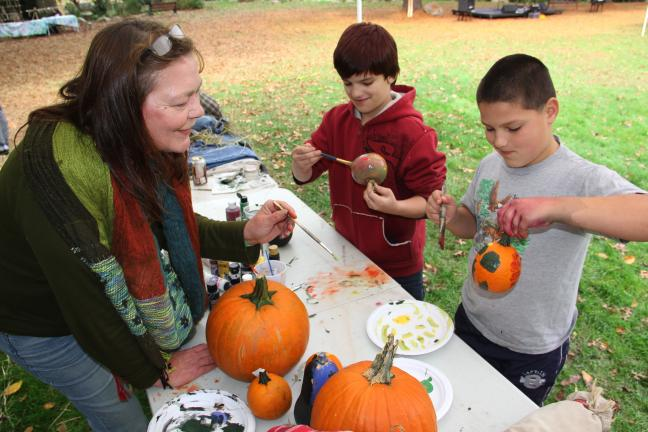 ANDREW LEIBENGUTH/TIMES NEWS Lehighton artist Susan Trainer helps Tyler Schalkhammer, 12, and Chris Zubris, 11, paint pumkins. Both boys are from Weatherly.