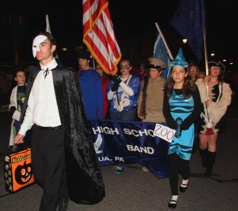 ANDREW LEIBENGUTH/TIMES NEWS Drum Major Jared Sharpe leads as the Tamaqua Raider Band continued its tradition of marching and playing in costume. Also pictured holding the banner is Jocelyn Rega.