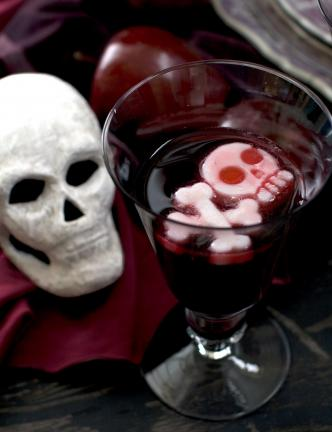 "This photo shows a ""goblet grave"" with yogurt frozen into the shape of a skull and crossbones floating in a glass of grape juice in Concord, N.H. (AP Photo/Matthew Mead)"