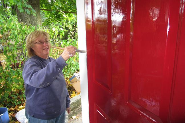 Gail Maholick/TIMES NEWS Kathy Henderson, a member of the Carbon County Assocation of Realtors, puts a coat of bright red paint on a door as part of the National Realtors Assocation request for local realtors to do a community service project during…