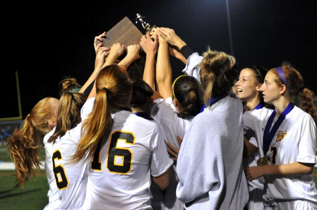 NANCY SCHOLZ/Special to THE TIMES NEWS Northwestern's girls soccer team hoists the District 11 Class 2A trophy high in the air after beating Blue Mountain on Thursday night.