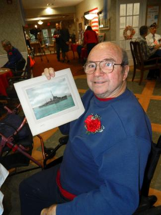 JUDY DOLGOS-KRAMER/SPECIAL TO THE TIMES NEWS Robert Smith, formerly of Lake Harmony, holds a photograph of the USS Eisner DE192. While in the Nayv, Smith served on the destroyer, which sailed in both the Atlantic and the Pacific during World War II.