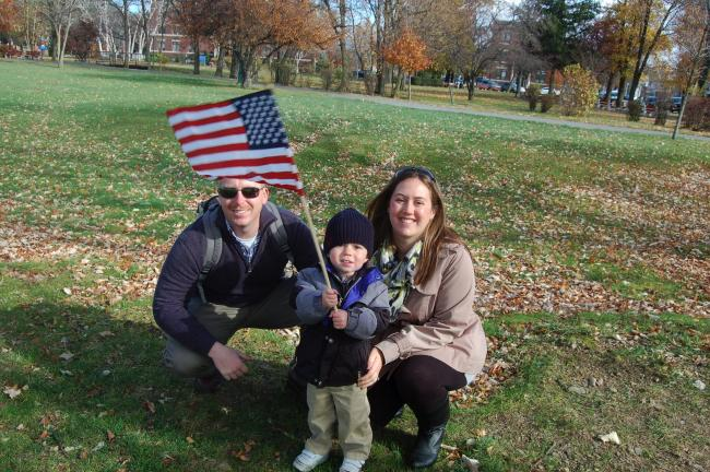 TERRY AHNER/TIMES NEWS  Flanked by his parents, Dave and Rachel Kannapel, Chase Kannapel, 2, of Yardley, shows his spirit as he waves this flag before the start of the Veterans Day dedication held in Palmerton on Monday.