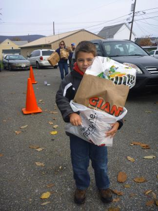 SPECIAL TO THE TIMES NEWS Cub Scout Tiger Joey Matla carries a Scouting for Food donation during the food drive held on Saturday.