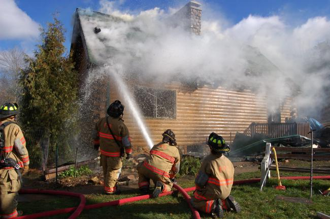 Gail Maholick/TIMES NEWS Firefighters battle a stubborn blaze at 887 Railroad Drive, Weatherly, on Wednesday. After beating down the flames, several times, the fire continued to burn through the roof.