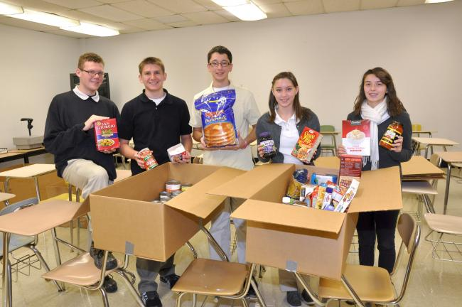 AMY MILLER/TIMES NEWS Five members of the Future Business Leaders of America chapter at Panther Valley High School look over just a few of the boxes of food items collected by the students during a recent food drive. The food was then distributed to…
