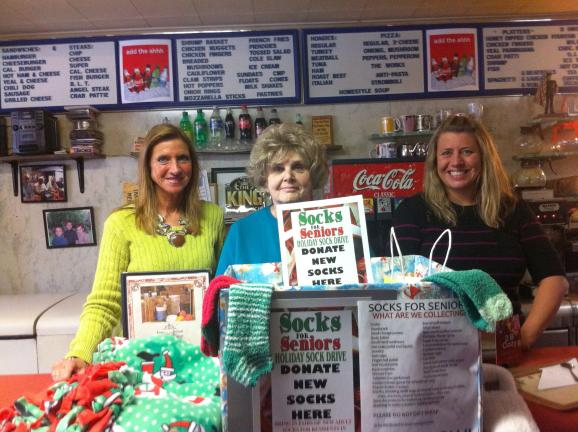 SPECIAL TO THE TIMES NEWS Mary Ann Dulaney, left; Ruth Weiss, owner of Tommy's Italian Restaurant, Coaldale; and Jess Kutza, with the Socks for Seniors boxes. Items can be dropped off at numerous businesses in Carbon and Schuylkill counties.
