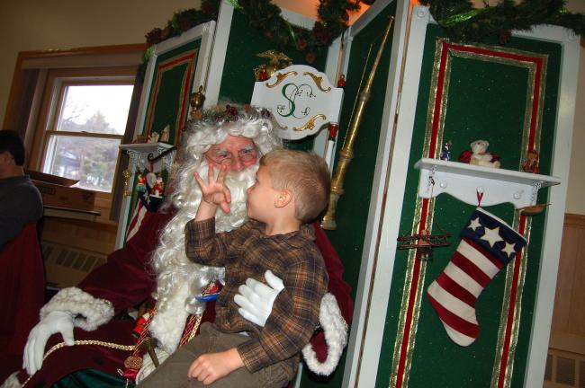 TERRY AHNER/TIMES NEWS Wyatt Rondeau, 5, of Pottsville, is clearly all beside himself as he tells Santa his toy wish list during the annual holiday dinner held Sunday at the Aquashicola Fire Company.