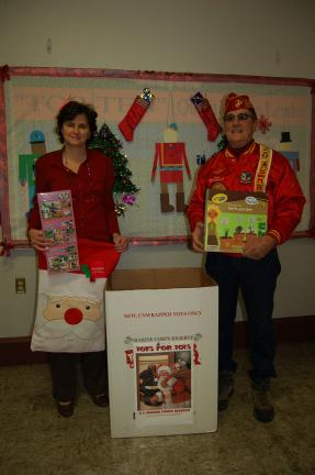 Gail Maholick/TIMES NEWS Sherry Sernak, principal at Ss. Peter and Paul Catholic School, Lehighton, presents toys and gifts which were collected at the school for the Toys for Tots program to Joe Balogach, member of the Schuylkill Carbon Marine…