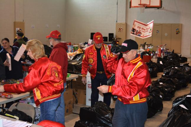 DONALD R. SERFASS/TIMES NEWS USMC veterans of the Schuylkill-Carbon Detachment 626, Marine Corps League's Toys for Tots program, work in sync Friday as they distribute holiday gifts to needy families at the Tamaqua Salvation Army Regional Community…