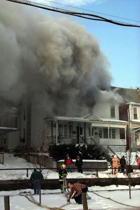 DONALD R. SERFASS/TIMES NEWS Firefighters often are exposed to heavy smoke, sometimes containing contaminants. This smoky fire was fought on Pleasant Row in Tamaqua on Jan. 18, 2000.