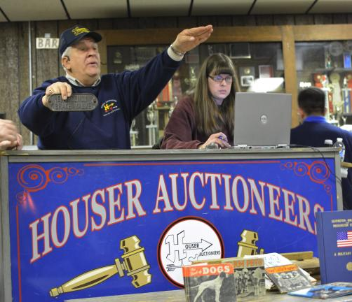 DONALD R. SERFASS/TIMES NEWS Auctioneer Doug Houser sells a vintage brass railcar plaque at Saturday's railroadiana auction at Mahoning Valley Fire Hall as clerk Jackie Zehner-Clemson tracks bids. The estate sale continues tomorrow in Schnecksville.