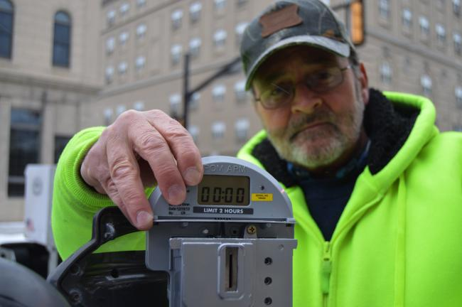 "KATHY KUNKEL/TIMES NEWS Dave ""Chip"" Christ places a new meter assembly into a parking meter along Broad Street in Tamaqua. The new meters will take quarters only, giving 30 minutes of time for each quarter, up to a two hour limit."
