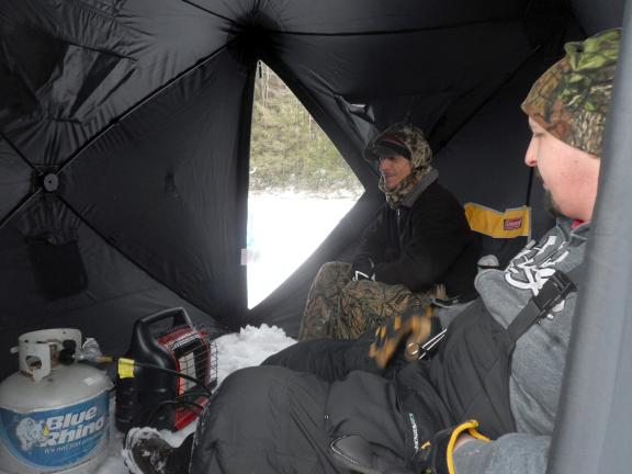 Dave Bloss sits in tent while ice fishing in Tuscarora.