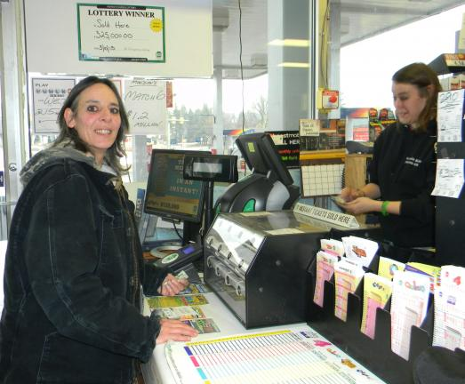 LISA PRICE/TIMES NEWS Barnesville resident Elizabeth Smith purchases a lottery ticket from My Hometown Mini Mart clerk Nicole Horack last week. The sign about the unclaimed $325,000 prize is on the wall to her left.