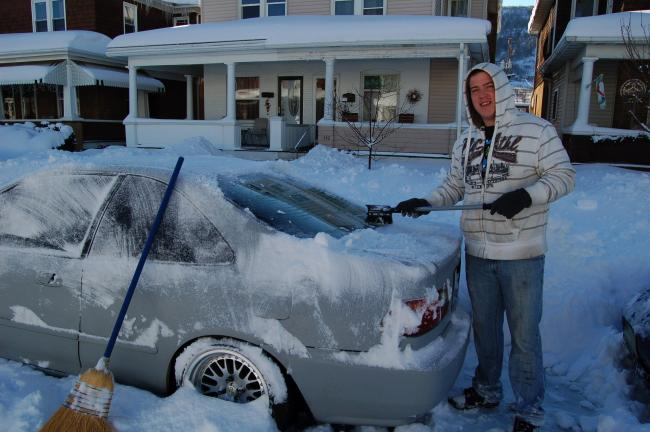 LINDA KOEHLER/TIMES NEWS Donald Stevens cleans his car off which is parked on Franklin Ave., Palmerton. Once he leaves, there's no guarantee he'll get a spot when he comes home.