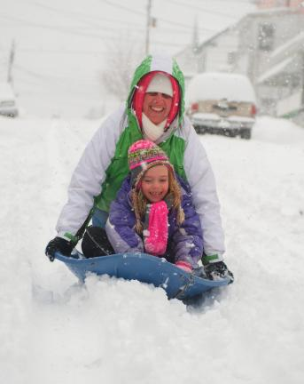 BOB FORD/TIMES NEWS  Christy McGeehan and 7-year-old Harmony Berk try to get their sled going down 6th Street in Jim Thorpe Thursday morning.