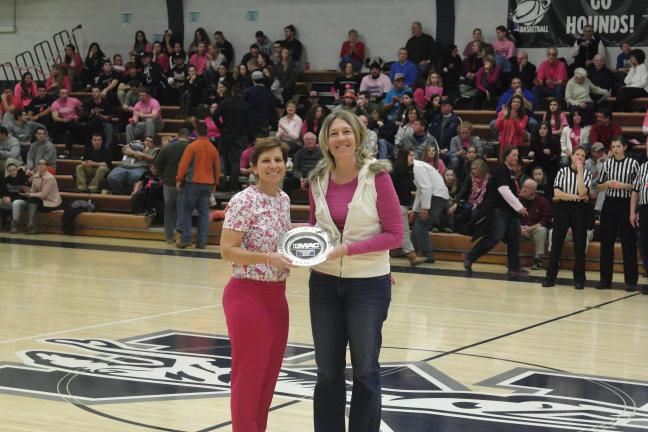 Robert Brands/Moravian Sports Information Office Moravian College women's basketball coach Mary Beth Spirk presents Kathy Beck DeKorte with her MAC Hall of Fame plate during halftime of Moravian's game against Juniata College recently.