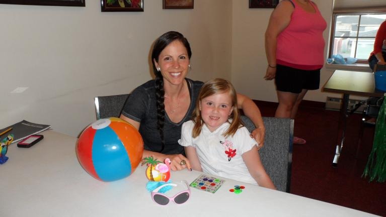 MARY TOBIA/SPECIAL TO THE TIMES NEWS A beach ball, palm trees, flip flops and sunglass set the tone for kindergartener Hadlee Lake and her mom Heather for some Beach Bingo at the Palmerton Area Library.