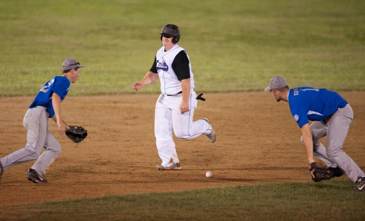 bob ford/times news Ryan Malarkey of the Franklin Township Shockers runs between second and third base as East Stroudsburg infielders Thomas Aruta (left) and Will Kazura go after the ball.