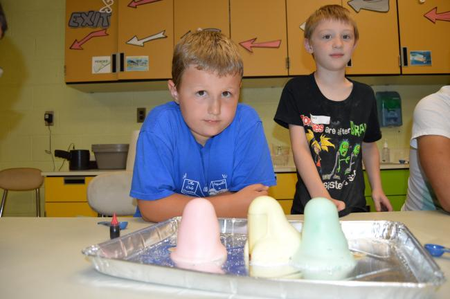 "LISA PRICE/TIMES NEWS Students Declan Coleman, left, and Loki Anderson-Hill watch the reaction from mixing items to make ""elephant toothpaste,"" so named because it expands to make enough toothpaste to use on an elephant."