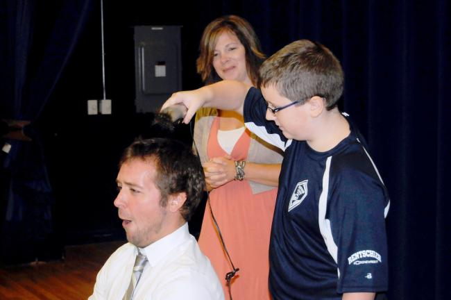 RON GOWER/TIMES NEWS Northern Lehigh Elementary Principal Scott Pyne grins as sixth-grade student Nicholas Miller cuts his hair during the student student assembly program. Miller earned the barbering rights by having the highest scores in a state…